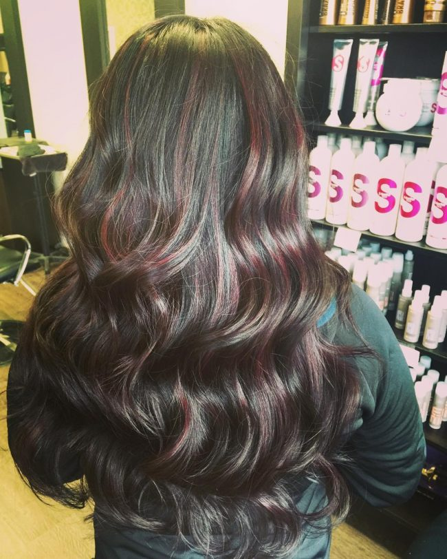 Wavy Black Curls with Muted Burgundy Highlights